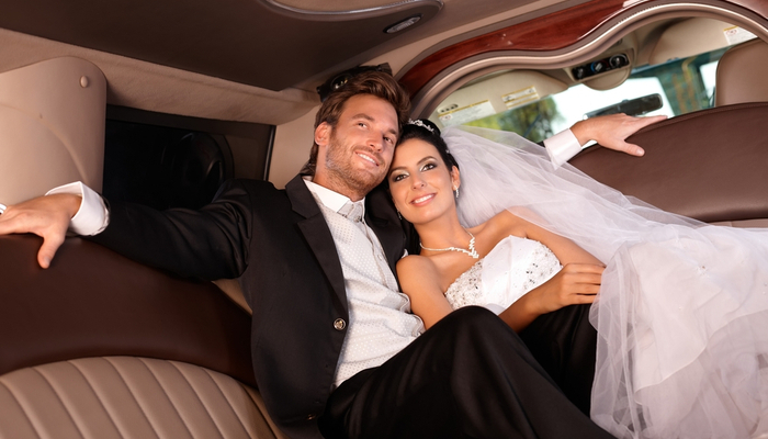 Bride and groom sitting in limousine with comfort while smiling happily on wedding day